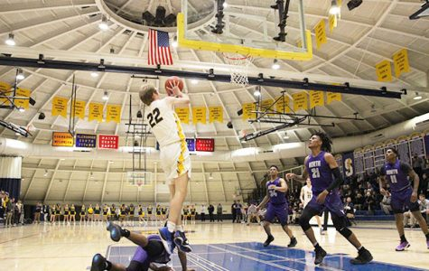 Jumping to the hoop, senior Gavin Morse goes up for a shot against the Niles North Vikings. The Titans beat the Vikings 70-59 on Dec. 7.