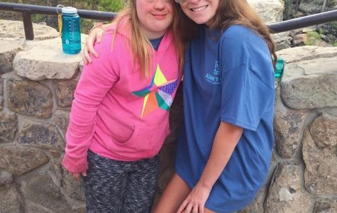 Molly's   mission:   Smiling with a camper, senior Molly Stryker (right) poses for a photo after a hike. Stryker spent a week at Adam's Camp over the summer.