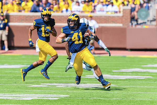 Running down the field, South alum Mike Hirsch makes his first play as a Wolverine. Hirsch graduated from GBS in 2010.