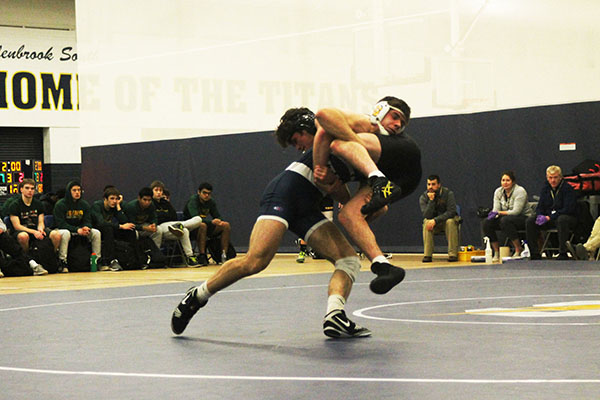 Carryin'   Crecan:   Taking down a Fremd wrestler, junior Norbert Crecan attempts to gain a win for the South varsity wrestling team. The Titans won the match against the Fremd Vikings 37--36. Photo by Dany Herrera