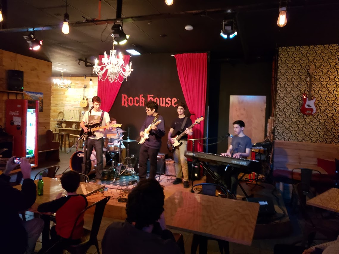 LIGHTING UP THE ROOM:   Performing onstage at the Rock House (from left to right) sophomores Danny McNeela, Sam Collett, Yeon Park, Jeremy Bernstein and Lev Sheinfeld have been playing together as the band Livingroom since August of 2018. In the future the band hopes to possibly record a new single for Spotify and iTunes.