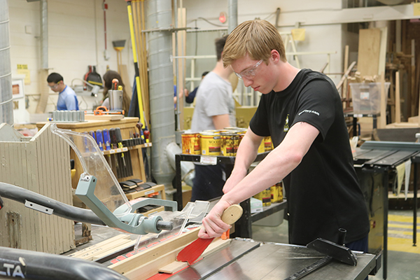 Holding a push stick to keep a piece of wood steady, sophomore Hunter Weisensel prepares to cut the wood for his project. There are four levels of woodworking offered at South.