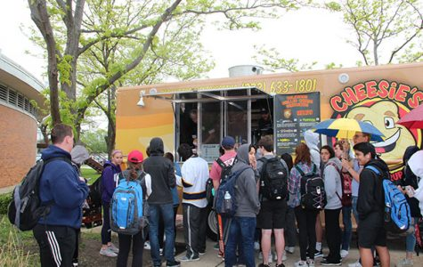 Waiting in line during the lunch blocks on May 17, students patiently stand outside in the rain to get a grilled cheese from Cheesie's food truck stationed in the autos courtyard. South's annual Spring Fling is intended to boost student morale and celebrate the rapidly approaching end of the year.