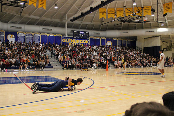 Boardin' Boron: Scootering across the gym floor, Band Director Brian Boron participates in a Titan Nation competition during the 2019 fall sports assembly on Sept. 13. The sports assemblies were brought back as a tradition due to help from junior Grace Diehl's Change.org petition.