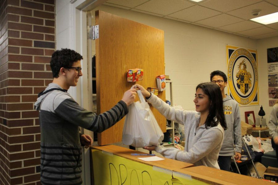Handing+Laya+Anvari%2C+senior+class+representative%2C+a+bag+of+donations+for+the+Food+Drive%2C+senior+Ben+Kalish+helps+provide+supplies+for+568+families+around+the+community.+The+food+drive+underwent+a+number+of+changes+this+year+to+emphasize+the+humanitarian+aspect+behind+the+donations.+