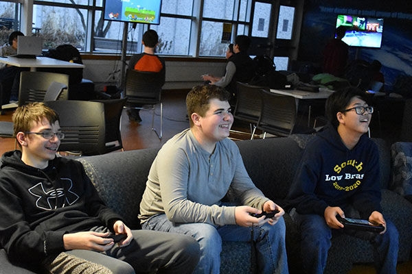 Grinning gamers: Jack Edgerly (left), Sean Minihane (middle), and Tim Walters (right) sit together in the SAC, enjoying their time at Gaming Club every Monday after school. Photo by Shoshana Green