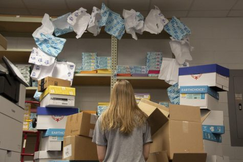 Surrounded by reams of paper, a student feels distressed about the amount of paper used daily here at South. Each day, the school uses 67,516 pieces of paper, of which 45,000 are printed in South's print shop.