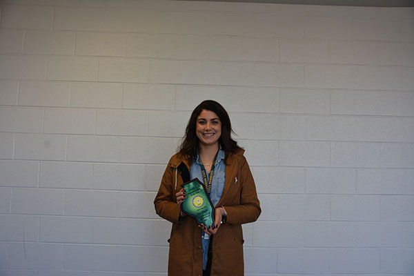 Awarding Ahlgrim: Holding her plaque after winning the Regional Head Coach of the Year Award, Meg Ahlgrim, varsity girls' tennis head coach, expressed surprise at being chosen after only one year of coaching the team.