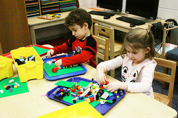 Toys AND Tots: Playing with LEGOs, two Titan Tots participate in their class time playing with toys.      South students have discovered passions for childhood education through through their experiences                 with Titan Tots.