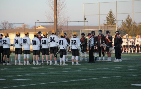 Lining up at center field, the boys' lacrosse team stands together at the start of a game in the 2019 season.