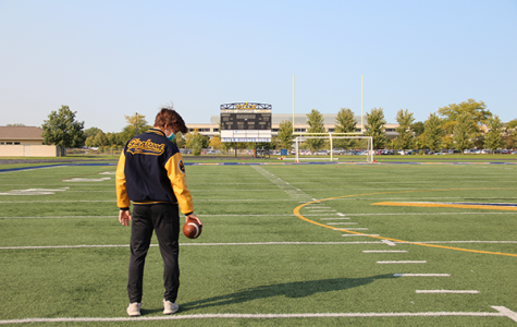 Melancholy Michael: Standing alone on the football field at John Davis Stadium, Varsity Quarterback Michael Bauer contemplates the arrival of his season. Because of IHSA regulations as a result of the coronavirus pandemic, the South football season will begin in February of this school year instead of August like normal