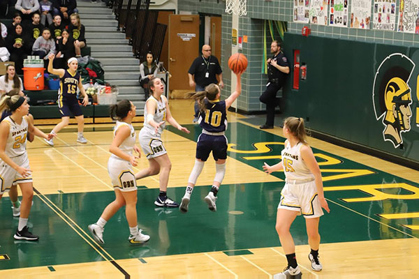 Rising Rogers: Dribbling up the court, sophomore Sidney Rogers, girls' basketball player, analyzes the defense at a basketball camp and finishing around the rim, Rogers goes up in traffic against Glenbrook North last year. Though she has only been at South for one full year, her impact on the varsity girls' basketball team has already been prevalent.