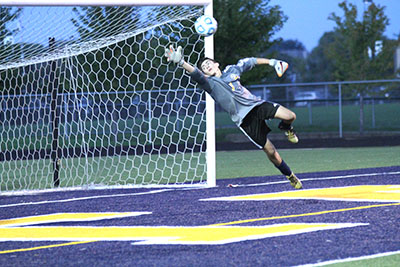 ADAMOPOLOUS IN THE AIR: Warming up for the game against Palatine, senior goalie Perry Adamopolous dives to save a shot on goal. The Titans are 7-6-2 so far this season.