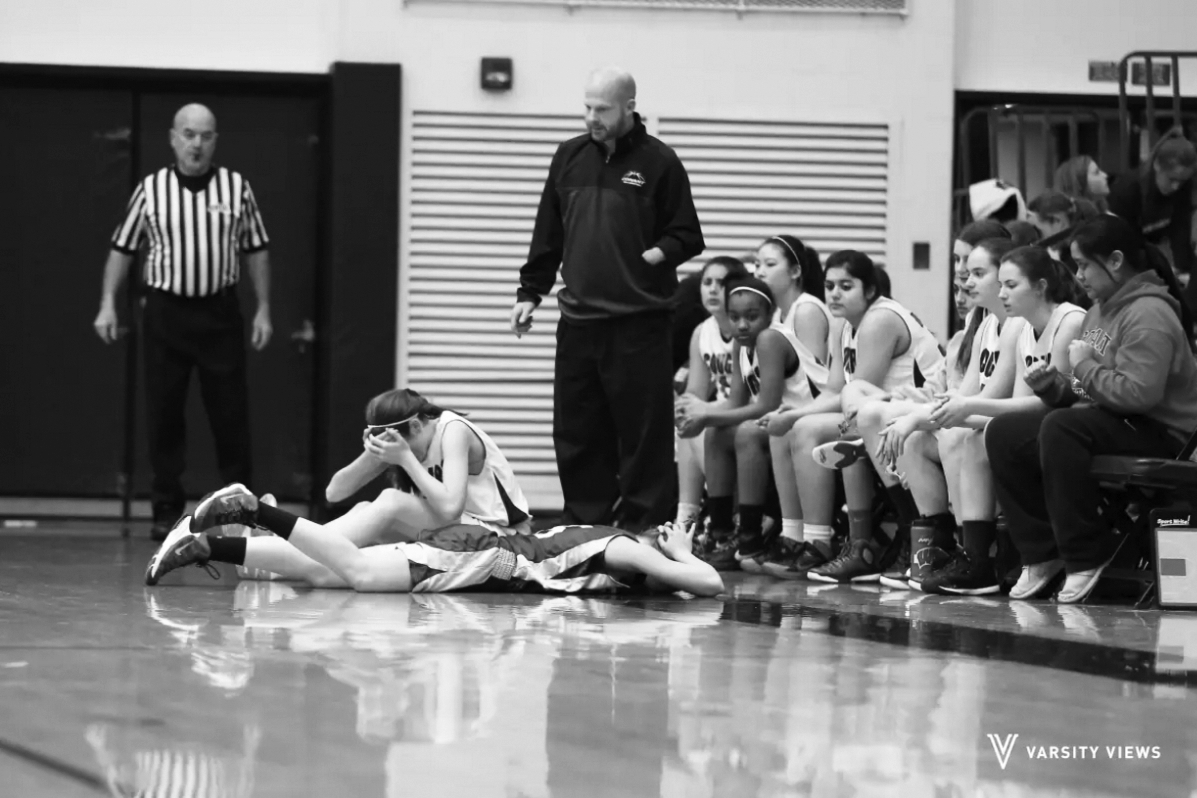 CONCUSSION DISCUSSION: Lying face down on the basketball court during a game on Jan. 13, sophomore Lauren Meier struggles with a head inury, later diagnosed as a concussion. By the next school year, Illinois middle and high schools must fit concussion management to state standards, according to the Youth Sports Concussion Safety Act.