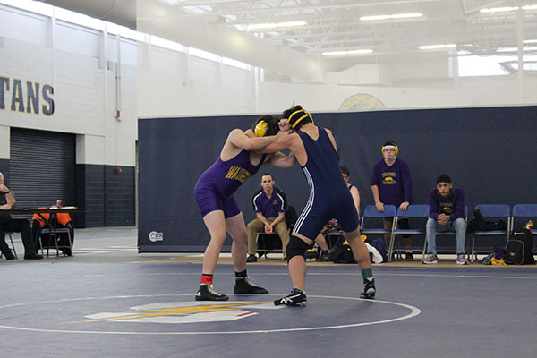 FIGHT TO THE FINISH: Junior Paul Jo goes head-to-head against a Waukegan wrestler on Jan. 16. Jo finished with an individual win (left). The men beat Waukegan with a final score of 51-24.