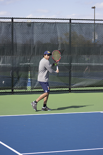HARD HITS: Swinging his racquet, senior Vinny Ahluwalia sets up to hit a forehand during preparation for his next match.