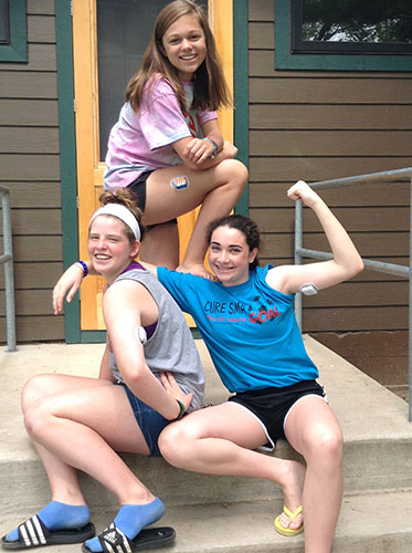 Standing outside of a cabin at an American Diabetes Association camp in northern Illinois, freshman Megan Stettler (top) and her fellow campers pose with their OmniPods, an insulin management system for type 1 diabetes. Stettler, as well as other South students, has worked to raise awareness and foster relationships with others affected by their illnesses.