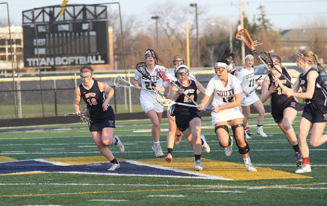 EYES ON THE PRIZE: Running past Oak Park River Forest defenders, Lindsey Karsh, junior midfield and attack (left) tries to keep cradling the ball while moving down the field during a game on April 14. The Titans beat Oak Park River Forest BY a score of 16-6.