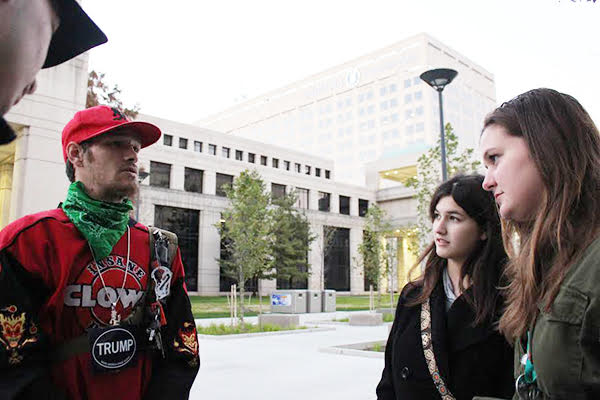 Civil Communication: Standing to the side, Oracle editors, Anne Marie Yurik (front) and Alexandra Sharp (back) interview a Trump supporter who attended the Trump resistance rally held in Indianapolis. The rally was used as a way for individuals to voice their concern of a Trump presidency. Photo by Yoon Kim
