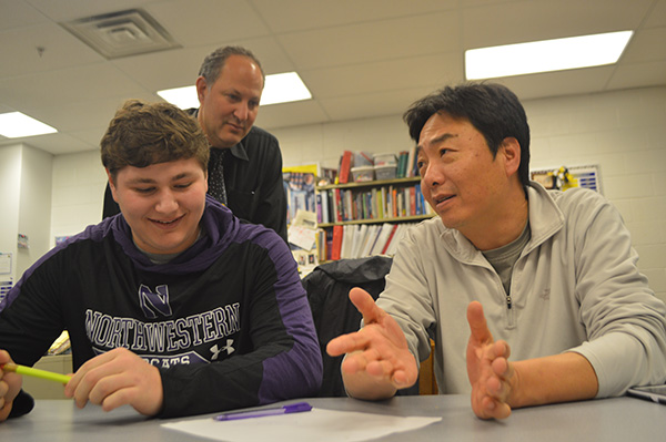 Father-son   Study   Session: Peering over his son Simon's shoulder, math teacher Steve Farber checks over the work done by his son and math teacher Steve Yoon.  The teachers have sons who attend South, and all three pictured recognize the change of dynamic between father and son due to their teaching positions.