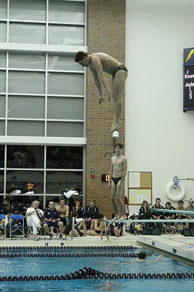 ACH IN THE AIR: Practicing before a dual meet during his senior year at GBS, Aaron Ach, current Princeton sophomore completes a pike dive. Ach now dives at Princeton.