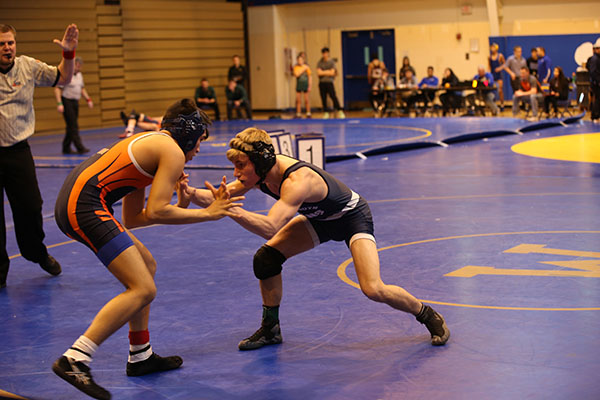 Preparing to take down his opponent, senior captain Ethan Bond, 132 pounds, wins against Bufflo Grove at the Regional tournament on Feb. 4. The team continues to improve each practice and meet and hopes to win a sectional title this Friday, Feb. 10, according to head coach Pat Castillo.