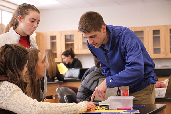 Methods   in   Motion:   Helping his students with a lab, Science Teacher Robert Cowhey explains the flow of electrical charge through a circuit. This year, Cowhey has not assigned any homework to his students, and he is one of several other teachers who have introduced unconventional teaching methods in their classes.