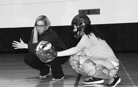 Friends   on   the   field:   Kneeling toward the ground, junior Winnie Tomsheck and Dana Boehmer, PE teacher and softball coach, go over technique for the catcher position. According to Tomsheck, she is appreciative of the bond she and Boehmer have formed through softball, which has led Tomsheck to look up to her coach as a role model. Photo by Sophie Mason