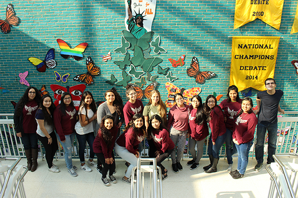 SOARing Toward Equality: Posing in front of Students Organized Against Racismís (SOAR) art display in the old pit, SOAR members admire their hard work. SOAR created the display with the intent to raise awareness for the hardships experienced by immigrants, with members Annabelle Manjooran, Sana Bouacha and Debby Kim coming in during spring break to work on the project alongside junior Lesly Zavalaís leadership to turn the clubís vision into a reality.