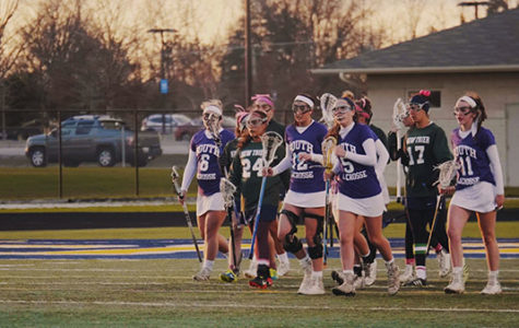The rest of the players on the field (right) walk back to the draw circle after scoring against the Trevians. The women lost to New Trier by a score of 14-7, according to captain Sophie Hensley.