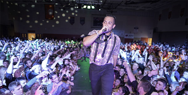 BOOMING WITH ENERGY: Riling up the students at Minooka High School, an MC walks down the catwalk at a dance facilitated by BOOM Entertainment. South also recently hired BOOM Entertainment to aid them in organizing the upcoming Homecoming dance, themed Windy City South.