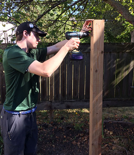 EAGER TO ACHIEVE EAGLE: Assembling a bird-feeder post, Life Scout Colb Uhlemann uses a drill to hang metal hooks in order to put up the bird feeder. Uhlemann makes the bird feeder post in The Grove for his Eagle Project, hoping to achieve Eagle Scout status for community service work. Photo courtesy of Will Dunk
