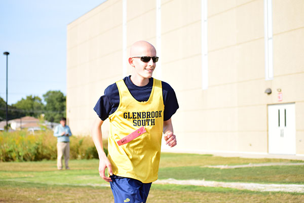 Running in a cross country race, freshman Luke Gregory smiles toward the finish line.