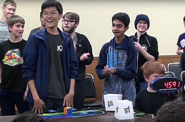 """SPEEDY STEVE: Standing up in amazement, senior Steve Cho smiles as he realizes he solved the 3x3 Rubik's Cube solve in 4.59 seconds at the 'ChicaGhosts 2017"""" on Oct. 28. Cho has been cubing since 2012, and over the course of five years he has attended thirteen American Cube Association competitions. Photo courtesy of Steve Cho"""