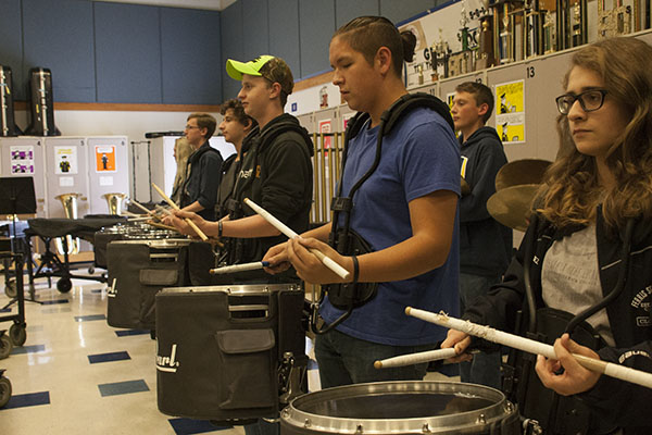 DEDICATED DRUMMERS: Members of South's drumline, junior Bryce Brennan, senior Michael Vilches and senior Grace Rodriguez (from left to right) diligently practice in the band room after school. The drumline is a close-knit group composed of 17 members, according to senior drum captain Michael Vilches.