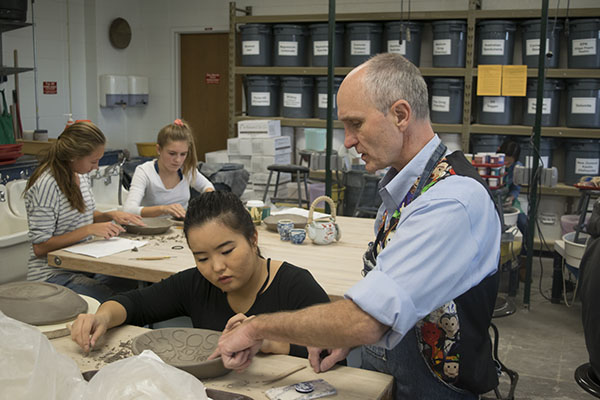 WONDERFUL WEBB: Ceramics teacher Kurt Webb instructs a student on her ceramics piece. Webb says he developed his passion for art at a young age.