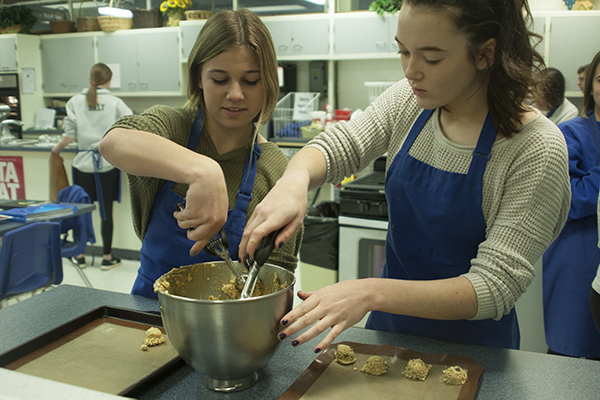 FANTASTIC FOODS:   Scooping cookie dough, freshman Dani Stadler (left) and Megan Butler (right) participate in foods one. They are preparing chocolate chip oatmeal cookies. Stadler plans on advancing to Foods two in the future because she loves learning about different foods and how to make them.