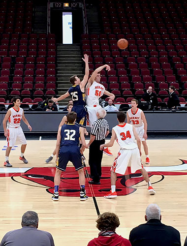 Starting a play, junior Mac Hubbard tries to tip the ball to one of his teammates. The Titans played at the United Center on Dec. 9 against Hersey high school and won 42- 38.