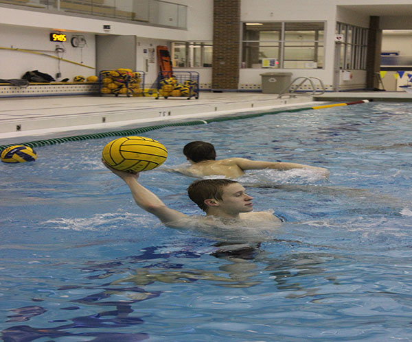 Getting ready to throw the ball, junior Ryan Meyers (left) looks for an open teammate to pass the ball to. Recieving the ball, junior Cameron Schulte catches a ball thrown to him during a morning practice. The waterpolo team has a 9-1 record so far this season