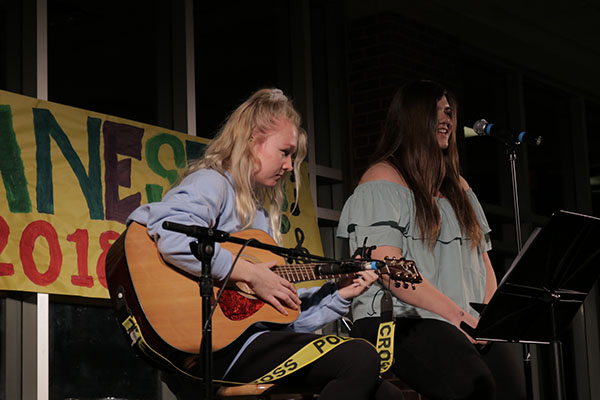 Strumming the guitar and singing into the microphone, sophomores Clare Dunne Murphy and Taylor Rudolph-Woitesek perform at Jamnesty on April 13. Several student bands at South perform at Jamnesty for peace and human rights.