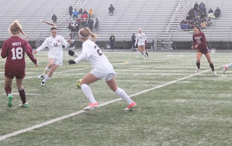 MEIER ON THE MOVE: Moving out of the way, sophomore Katie Weiss assists captain Lauren Meier as she dribbles away from a Loyola player. The Titans game against Loyola was an important one because it kept both teams undefeated.