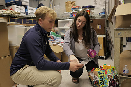 PROUD PRESIDENT:  Labeling a box of donated food, 2017-2018 Student Body President Abby Grant talks things over with junior Matthew Baumstark. Grant oversaw changes to the canned food drive, amongst other revisions made this year.