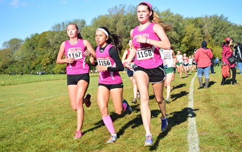 Running together (right), junior Gigi Walsh (left), senior Catherine Nowak (center) and sophomore Alex Kleemen (right) continue to finish the meet. The Titans placed fifth overall at Regionals on Oct. 28.