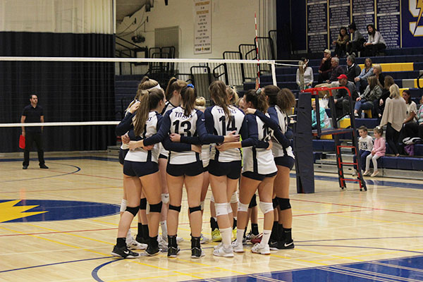 Huddling before a play, the girl's volleyball team competes for a chance to make a playoff run. The girls' season ended when they lost to Loyola on Oct. 25.