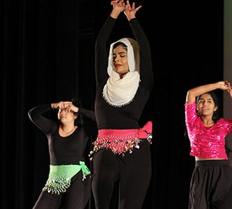 """Shakin' Shareef:   Moving in time to the music, senior Zainab Shareef dances onstage amongst her orchisisters. The 2018 Dance Show """"Captivate"""" was on Friday, Dec. 7."""
