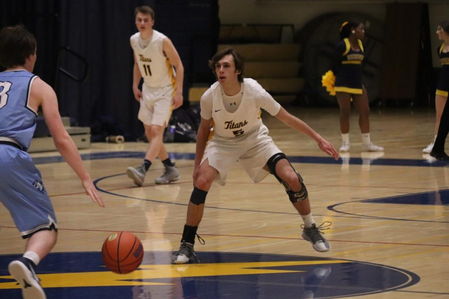 Baskets+with+braces%3A+++Defending+the+ball+against+Prospect%2C+senior+Tyler+Nelson+wears+a+brace+to+protect+his+knee.+He+has+suffered+two+ACL+tears+in+his+basketball+career.+Photo+by+Quinn+Toomey
