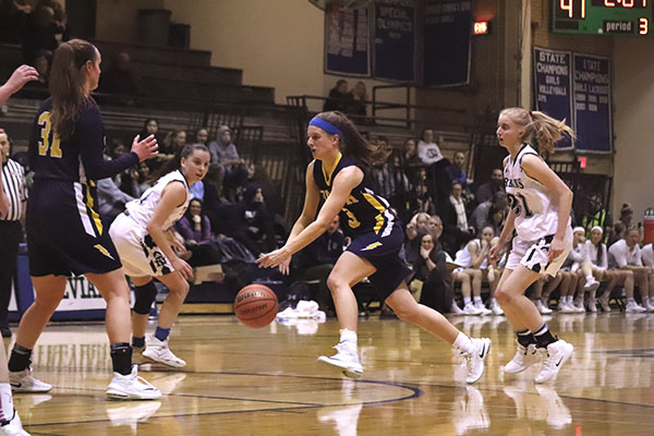 Dribbling through the defense, senior Libbie Vanderveen (center) attempts to score against the New Trier Trevians on Feb. 1. The Titans lost to the Trevians by a score of 60 - 33.