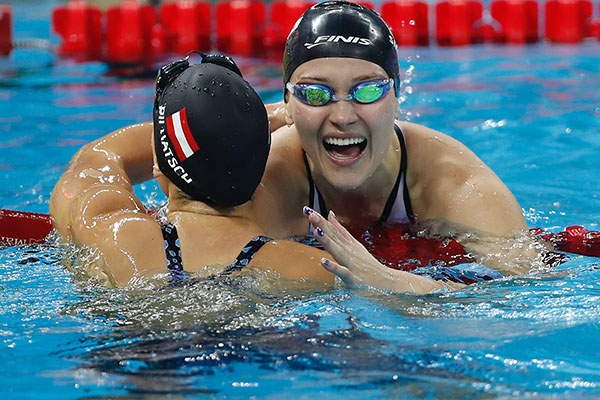 Olivia Smoliga (right) hugs Austrian swimmer, Caroline Pilhatsch, at the FINA World Swimming Championships after finishing the 50-meter backstroke on December 15, 2018. Smoliga placed first, beating Pilhatsch by 0.11 seconds.