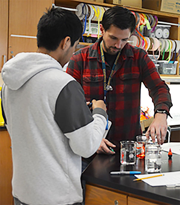 Helping Hands: Instructional Assistant Brendan Jacobi aids a student with his lab in a chemistry concepts class.
