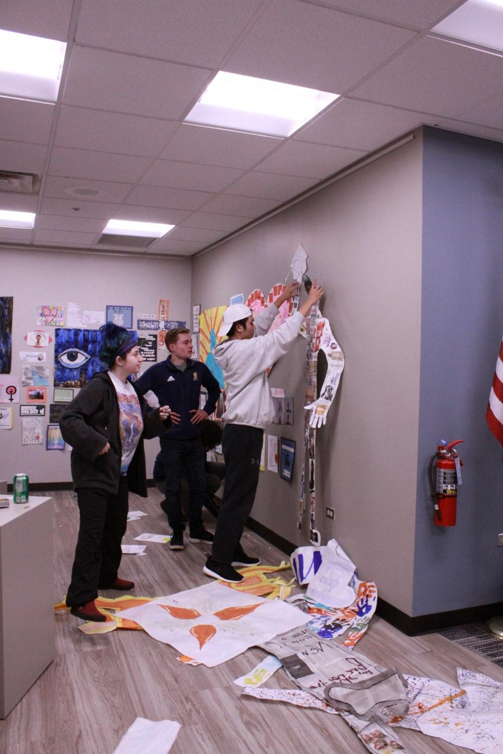 Seniors part of the Senior Summit design committee work together to hang up the artwork in the gallery.  According to senior Colin McCarthy (middle), their goal was to create a united collage from all art submissions.